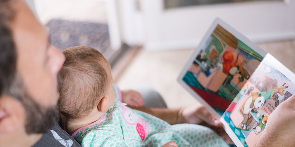 Man holding a baby reading a children's story